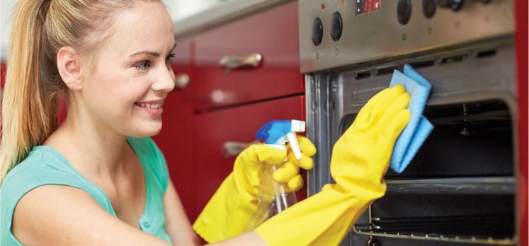 photo of a female cleaner cleaning an oven