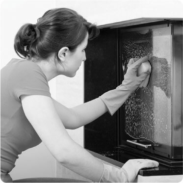 photo of a female cleaner cleaning s glass book shelf