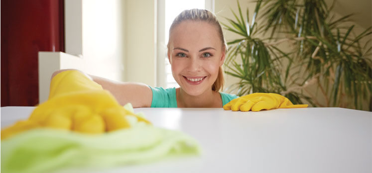 a female cleaner cleaning a table with a smile on her face
