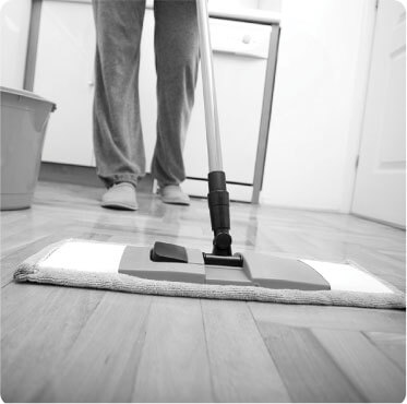 photo of a cleaner cleaning a wooden floor with a mop